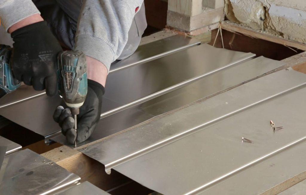 aluminium spreader plates being screwed over a timber joist floor.