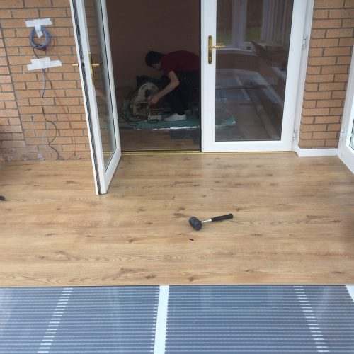 An electric carbon film floor heating system installed with an oak laminate flooring